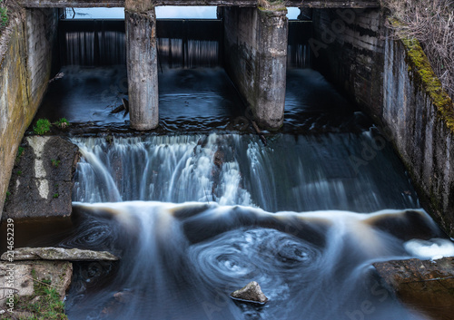 Concrete structure of the old river dam  Water blurred by long