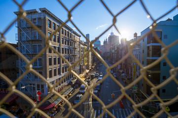 NEW YORK - CIRCA AUGUST, 2017: Downtown Manhattan and Chinatown viewed through a chainlink fence on the Manhattan Bridge.