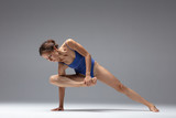 Young beautiful yoga woman is posing in studio - 214672672