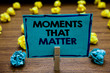 Handwriting text Moments That Matter. Concept meaning Meaningful positive happy memorable important times Blurry wooden deck yellow and blue lob on ground paper clip grip page with text.