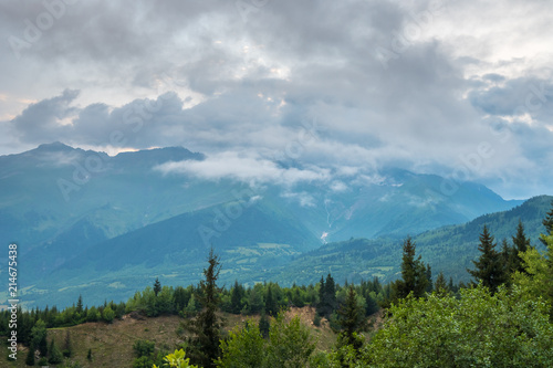 Aluminium Blauwe jeans Svaneti mountain landscape with green grassy hills, snowy peaks and white clouds on summer day, Georgia