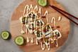 Uramaki Sushi Rolls or Nori Maki Topped with White and Brown Sauce