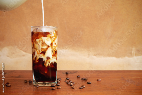 Foto Murales Pouring milk into a glass of homemade cold brew coffee on wooden table