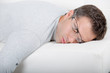 Man asleep on sofa, glasses being pushed off of his face