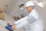 carpenters sanding with electric sander - 214730453