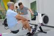 Leinwanddruck Bild - senior man in gym using a rowing machine