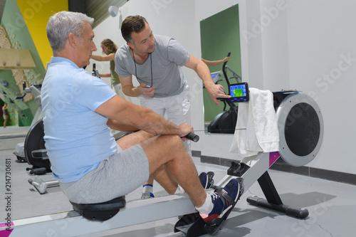 Leinwanddruck Bild senior man in gym using a rowing machine