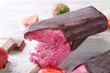 Tasty strawberry ice-cream with chocolate on table, closeup