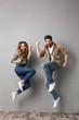 Leinwandbild Motiv Full length portrait of a cheery young couple jumping