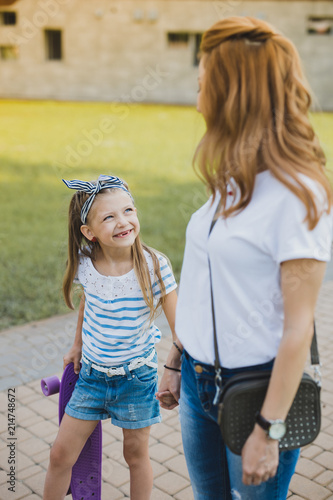 Foto Spatwand Skateboard Violet skateboard. Caring stylish mother feeling relaxed while taking her girl with violet skateboard to the park