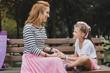 Having conversation. Cute preschool daughter having nice conversation with her appealing mother