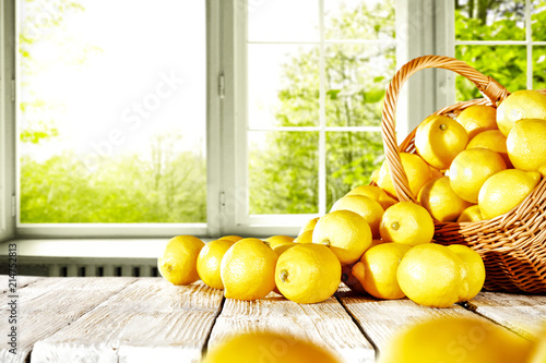 Leinwanddruck Bild Fresh yellow lemon on white wooden table and free space for your bottle or glass. Window background of summer time.