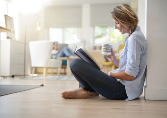 Beautiful 30-year-old woman relaxing with book and hot tea