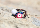 greek jewelry advertisement on the beach with evil eye and semi precious stones