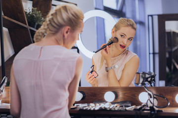 Fishbone braid. Blonde-haired woman with fishbone braid putting makeup on while sitting near big light mirror © zinkevych