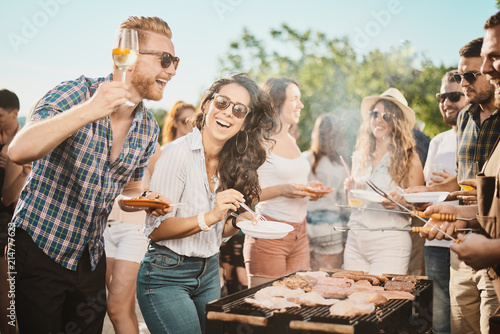 Group of people standing around grill, chatting, drinking and eating.  - 214777623