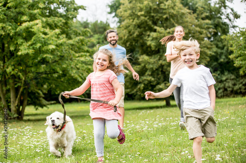 Leinwanddruck Bild Junge und Mädchen mit Hund im Park