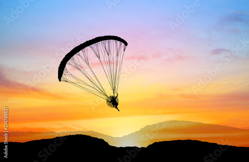 silhouette Para-motor flying on the sky  at sunset © rathchapon
