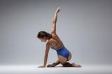 Young beautiful yoga woman is posing in studio - 214793461