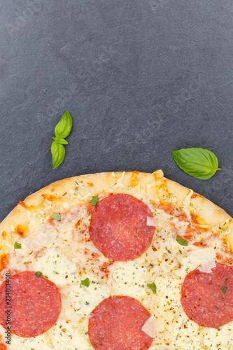 Leinwandbild Motiv Pizza Salami von oben Textfreiraum Copyspace Hochformat Nahaufnahme Schieferplatte