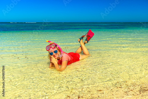 Foto Spatwand Zwavel geel Happy woman with snorkeling wetsuit, mask and fins pink and peach color, lying in the tropocal sea. Female enjoying in Hangover Bay, Nambung National Park, Western Australia.Summer holidays.Copy space