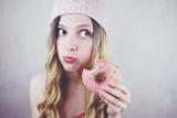 Retrato divertido de una mujer joven y rubia con un donut rosa  - 214817626