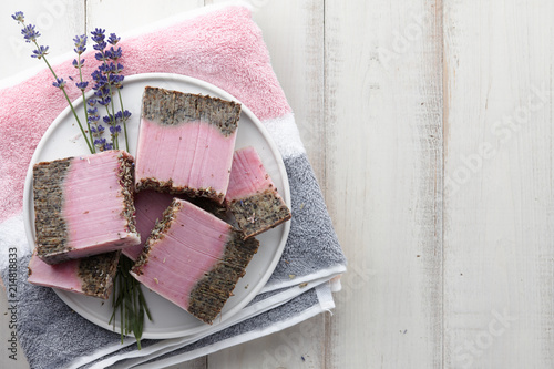 Handmade lavender soap, bath towel and flower blossoms on white wooden background. Natural cosmetics concept.