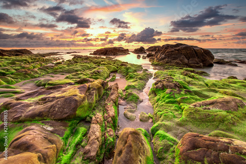 Foto Spatwand Zalm view of beautiful sunset sky at unknown beach in Sabah, Malaysia. Natural coastal rocks covered by green moss on the ground. soft focus due to long expose.