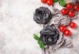 Black uncooked pasta  with tomato and basil - 214843050