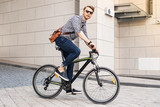Fast vehicle. Smart handsome man riding a bike in the city while going to work in the office - 214846651