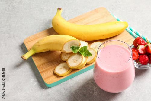 Leinwanddruck Bild Glass with tasty strawberry smoothie on table