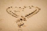A heart shape made on a sandy beach. - 214864296