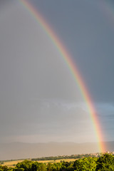 Rainbow over a quaint village and meadows, after the rain, copy space, wallpaper. © viperagp