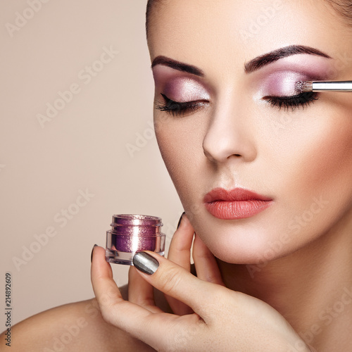 Leinwandbild Motiv Makeup artist applies eye shadow. Beautiful woman face. Perfect makeup. Makeup detail. Beauty girl with perfect skin. Nails and manicure