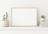 Home interior poster mock up with horizontal metal frame, succulents in basket and pile of books on white wall background. 3D rendering. - 214904225