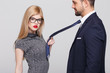 Leinwanddruck Bild - Sensual blonde manipulator woman with red lips pulling man by tie