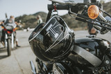 Close up of black helmet hanging from a classic black motorcycle handlebar. - 214918848