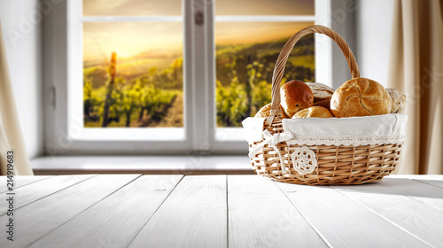 Foto Murales Fresh bread on white wooden table and window background. Free space for your decoration.