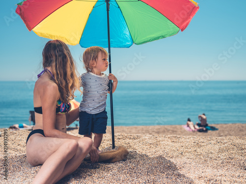 Foto Murales Mother with toddler under parasol on beach
