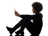one mixed race african young teenager girl woman using telephone in studio shadow silhouette isolated on white background - 214943842