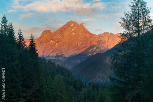 Dramatic sunset in  Dolomites Alps Mountain. Italy. Forest mountain sunset. Pink Mountain peak © georgeoprea9