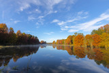 Autumn colored trees reflect on the water in the lake