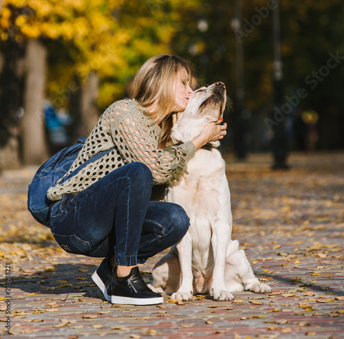 Leinwanddruck Bild Beautiful young blonde is walking in the park with her labrador in the park in the fall. The woman crouched beside her retriever.