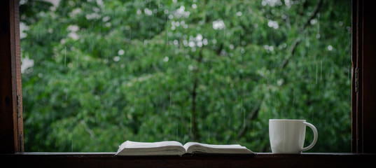 Cozy summer still life: cup of hot coffee and opened book on vintage windowsill and rain outside. Apartment. Rain in the summer © nastyaofly