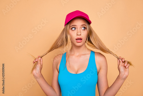 Leinwandbild Motiv Portrait of young attractive nice cute straight-haired blonde funky girl wearing casual, bright pink cap, tearing, pulling her hair curls. Isolated over beige background