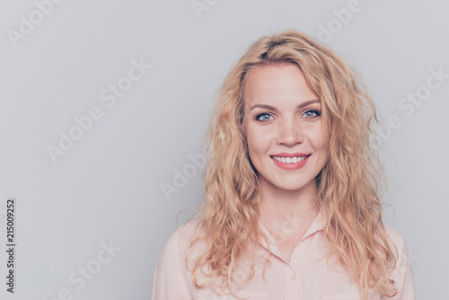Leinwanddruck Bild Portrait of young attractive nice cute caucasian smiling curly-haired blonde girl wearing casual shirt. Isolated over grey background
