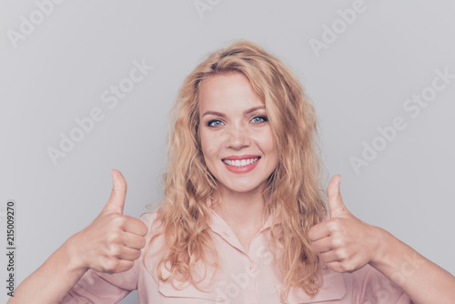 Leinwandbild Motiv Portrait of attractive cute curly-haired blonde gorgeous pretty girl wearing casual shirt showing two thumbs up signs. Isolated over grey background