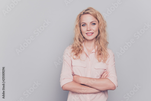 Leinwanddruck Bild Attractive cute curly-haired blonde gorgeous young girl wearing formal wear shirt with folded hands. Copy space. Isolated over grey background