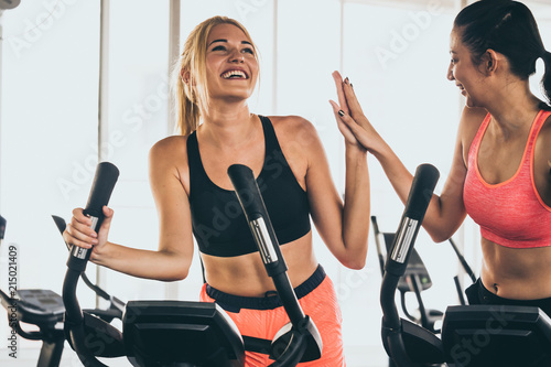 Leinwandbild Motiv Attractive young women working out together on exercise bike at the gym.
