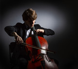Young man playing the cello. Portrait of the cellist on a dark background. - 215027004